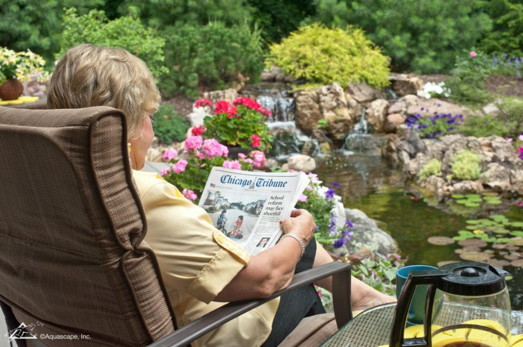 sitting by pond reading newspaper